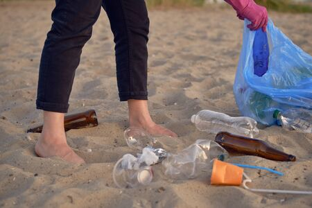 Young responsible human is walking with a blue garbage bag along a dirty beach of the river and cleaning up trash, old glass and plastic bottles, cups, tubules. Riverside pollution. Volunteering concept. Preservation of nature. Close-up shot. Reklamní fotografie