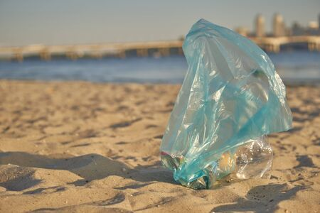 Blue bag with garbage lies on a beach of a picturesque river. Cleaning up trash. Volunteering concept. People and ecology. Riverside pollution. Preservation of nature. Close-up shot, top view.