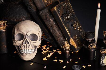 Realistic model of a human cranium with white teeth, old pot, burning candle, books with spells and jars of potion are on a wooden dark table. The petals of dried roses are scattered nearby. Black background. Medical science or Halloween horror concept. Magic, wizardry, miracles. Close-up shot.