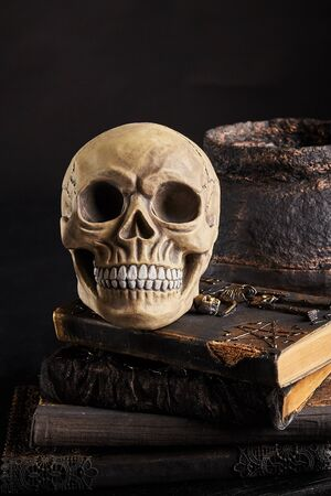 Realistic model of a human skull with teeth on an old books against a dark pot. Black background. Medical science or Halloween horror concept. Magic, wizardry, miracles. Close-up shot.