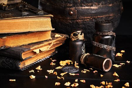 Some books with spells, old pot, jars of potion are on a wooden dark table. The petals of dried roses are scattered nearby. Black background. Halloween horror concept. Magic, wizardry, miracles. Close-up shot.