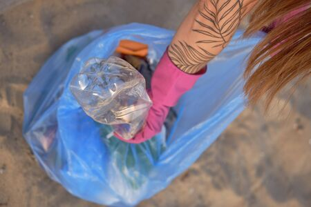 Young girl collects trash in a garbage bag, old glass and plastic bottles. Riverside pollution. Volunteering concept. Preservation of nature. Close-up shot.