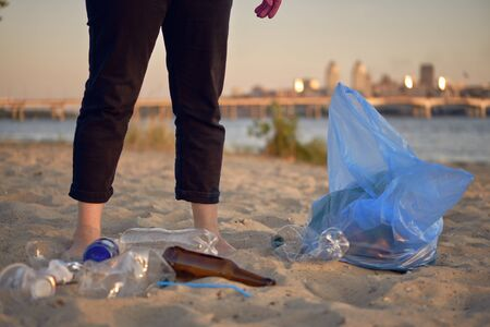 Conscious young female in pink rubber gloves is walking with garbage bag along a dirty shore of the river and cleaning up trash, old glass and plastic bottles. Riverside pollution. Volunteering concept. Preservation of nature. Close-up shot. Banco de Imagens