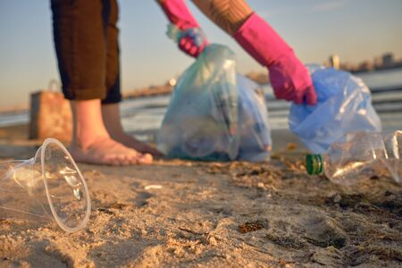 Responsible person in purple rubber gloves is walking with garbage bag along a dirty beach of the river and cleaning up trash. People and ecology. Riverside pollution. Volunteer concept. Preservation of nature. Close-up shot. Banco de Imagens