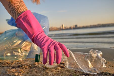 Responsible student in purple rubber gloves is walking with garbage bag along a dirty shore of the river and cleaning up trash, plastic bottle. People and ecology. Riverside pollution. Volunteer concept. Preservation of nature. Close-up shot.