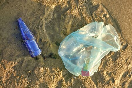 Used blue glass bottle and garbage bag lies on the river beach. Cleaning up trash. People and ecology. Riverside pollution. Preservation of nature. Volunteering concept. Close-up shot.