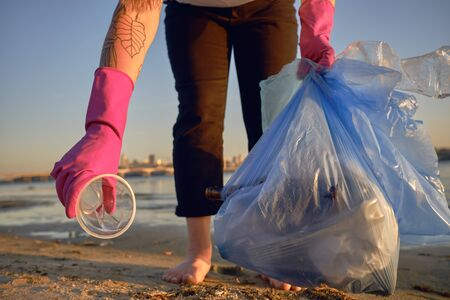 Conscious person in purple gloves is walking with garbage bag along a dirty beach of the river and cleaning up trash, plastic cup. People and ecology. Riverside pollution. Volunteer concept. Preservation of nature. Close-up shot.