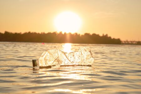 Crumpled transparent plastic bottle floats on the surface of the water. Sunset, green trees. People and ecology. Riverside pollution. Preservation of nature. Volunteering concept. Close-up shot.