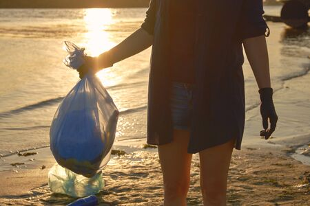 Young maiden in black gloves is walking with garbage bag along a dirty beach of the river and cleaning up trash. Sunset. People and ecology. Riverside pollution. Volunteer concept. Preservation of nature. Close-up shot.