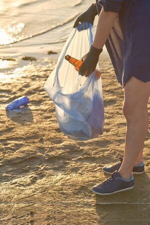 Young maiden in black rubber gloves is walking with garbage bag along a dirty shore of the river and cleaning up sweepings, used bottles. Riverside pollution. Volunteering concept. Preservation of nature. Close-up shot. Zdjęcie Seryjne