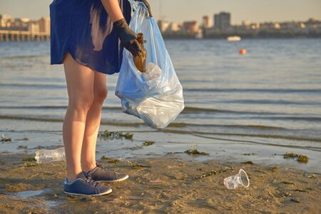 Young lady in black rubber gloves is walking with garbage bag along a dirty beach of the river and cleaning up rubbish. People and ecology. Riverside pollution. Preservation of nature. Close-up shot. Zdjęcie Seryjne