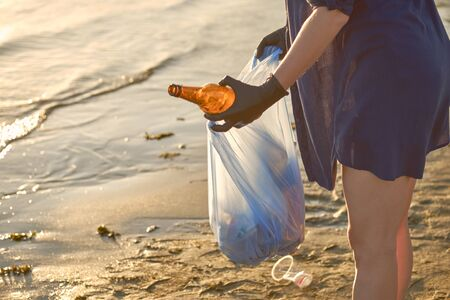 Young woman in black rubber gloves is walking with garbage bag along a dirty beach of the river and cleaning up rubbish, used glass bottles. People and ecology. Riverside pollution. Preservation of nature. Close-up shot.