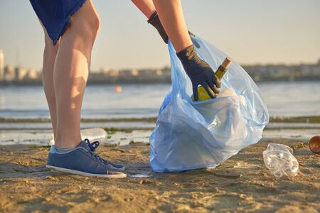 Young student in black gloves is walking with garbage bag along a dirty beach of the river and cleaning up litter, used glass and plastic bottles. People and ecology. Riverside pollution. Volunteer concept. Preservation of nature. Close-up shot.