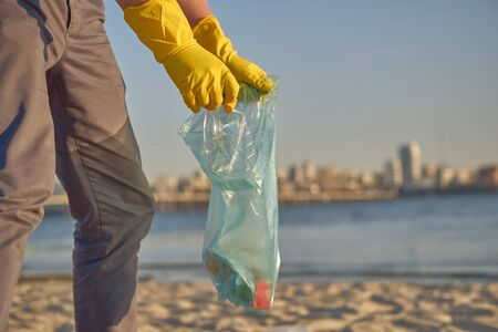 Responsible volunteer in yellow rubber gloves is walking with garbage bag along a dirty shore of the river and cleaning up trash. People and ecology. Riverside pollution. Preservation of nature. Close-up shot.