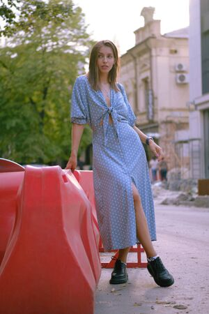 Blonde girl in long blue dress and a small black handbag on her shoulder Stock Photo