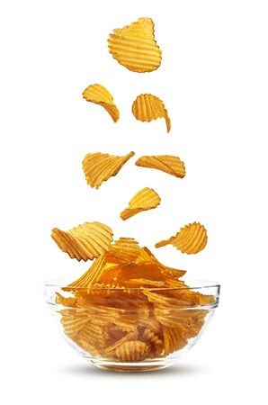 Grooved potato crisps falling down in glass bowl, isolated on white background with copy space for text, images. Crispy chips. Advertising. Close-up. Stock Photo