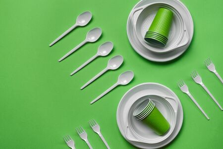 Colorful plastic disposable tableware, such as plates and bowls, five spoons and six forks, folded cups on green background with copy space. The concept of picnic utensil. Also used in fast food restaurants, takeaways. Top view. Selective focus. Close-up shot.