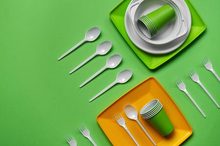 Colorful plastic disposable cutlery, such as plates and bowls, five spoons and six forks, folded cups on green background with copy space. The concept of picnic utensil. Also used in fast food restaurants, takeaways. Top view. Selective focus. Close-up shot.