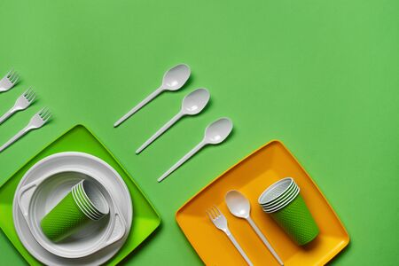 Colorful plastic disposable tableware, such as plates and bowls, four spoons and forks, folded cups on green background with copy space. The concept of picnic utensil. Also used in fast food restaurants, takeaways. Top view. Selective focus. Close-up shot.