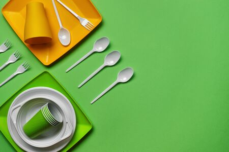Colorful plastic disposable cutlery, such as plates and bowls, four spoons and forks, folded cups on green background with copy space. The concept of picnic utensil. Also used in fast food restaurants, takeaways. Top view. Selective focus. Close-up shot.