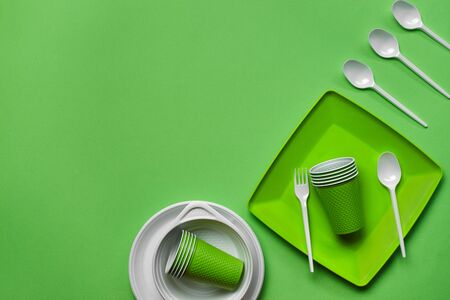 Colorful plastic disposable tableware, such as plates and bowls, four spoons, fork and folded cups on green background with copy space. The concept of picnic utensil. Also used in fast food restaurants, takeaways. Top view. Selective focus. Close-up shot.