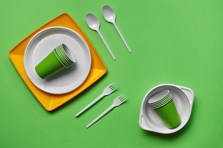 Buntes Einweggeschirr aus Kunststoff, wie zwei Teller, Löffel, Gabeln, gefaltete Tassen und eine Schüssel auf grünem Hintergrund mit Kopierraum. Das Konzept des Picknick-Utensils. Auch in Fast-Food-Restaurants, Imbissbuden verwendet. Ansicht von oben. Selektiver Fokus. Nahaufnahme.