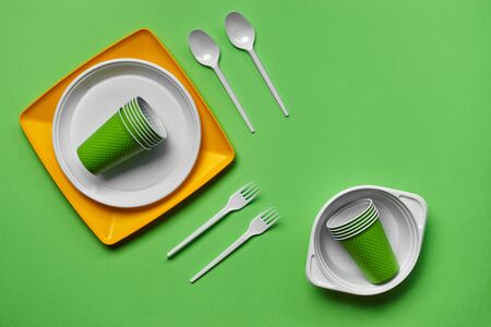 Colorful plastic disposable tableware, such as two plates, spoons, forks, folded cups and one bowl on green background with copy space. The concept of picnic utensil. Also used in fast food restaurants, takeaways. Top view. Selective focus. Close-up shot.
