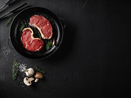 Raw juicy steaks with seasonings in an iron grilling pan, black background. Fresh meat, herbs, garlic, pepper, salt, champignon, iron tongs. Ingredients for cooking, restaurant concept. Close-up shot. Top view. Dry aged