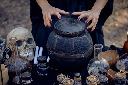 Witch in a black dress. She is making a magic potion in a dark pot while posing in a pine forest standing by the table with accessories for spells and witchcraft, smoke. Close-up. Stock Photo - 133618051