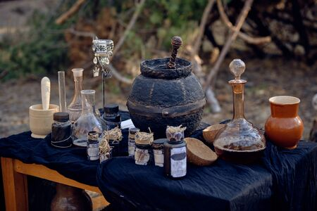 Table with accessories for spells and witchcraft standing in a pine forest. Magic potion is brewed in a black pot. Close-up shot.