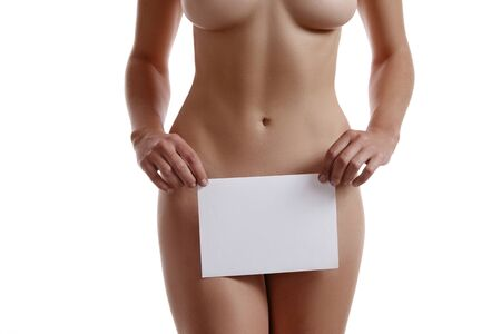 Perfect, slim, nude, young body of a beautiful lady covering her genitals with a sheet of paper while posing isolated on white. Beauty treatment. Plastic surgery and aesthetic cosmetology concept. Augmentation or reduce of a breast, cellulite removal. High resolution, close-up shot. 写真素材