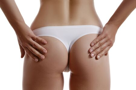 Woman in panties is touching her buttocks, posing back to the camera, isolated on white. Plastic surgery and aesthetic cosmetology concept. Close-up.