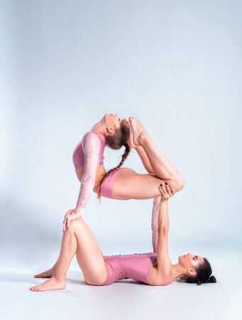 Two flexible girls gymnasts in beige leotards performing complex elements of gymnastics using support, posing isolated on white background. Close-up.