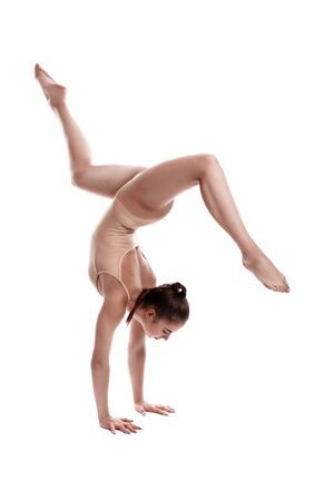 Flexible girl gymnast in beige leotard is performing an exercise standing on her hands while posing isolated on white background. Close-up. Zdjęcie Seryjne