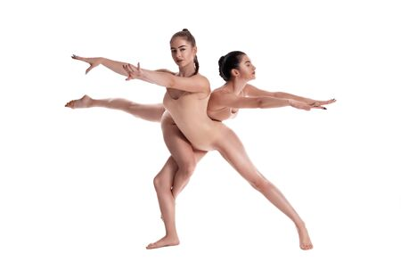 Two flexible girls gymnasts in beige leotards are performing exercises using support and posing isolated on white background. Close-up.