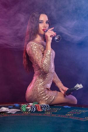Girl playing poker at casino, holding money, drinking champagne. Sitting on table with chips, cash on it. Black, smoke background. Close-up.