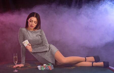 Girl in gray dress playing poker at casino, holding cards, laying on table with chips and champagne on it. Black, smoke background. Close-up.
