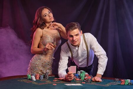 Man and woman playing poker at casino, celebrating win at table with stacks of chips, cards, champagne. Black, smoke background. Close-up. Stok Fotoğraf