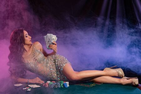 Girl in golden dress playing poker at casino, holding cash, laying on table with chips, cards on it. Black, smoke background. Gambling. Close-up.