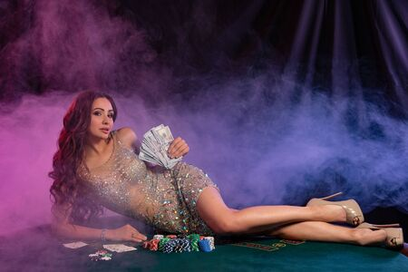 Girl in golden dress playing poker at casino, holding cash, laying on table with chips, cards on it. Black, smoke background. Gambling. Close-up. Фото со стока
