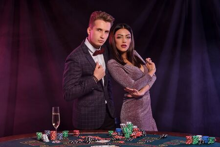 Man and woman playing poker at casino, celebrating win at table with stacks of chips, money, cards, champagne. Black background. Gambling. Close-up. Stok Fotoğraf