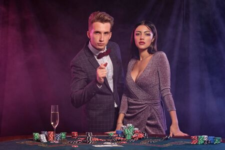 Man and woman playing poker at casino, celebrating win at table with stacks of chips, money, cards, champagne. Black, smoke background. Close-up.