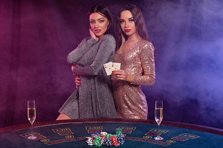 Two girls are playing poker at casino, hugging, holding cards, posing at a table with chips, champagne on it. Black, smoke background. Close-up.