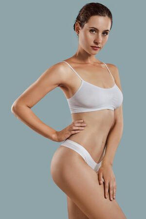Young woman in white underwear, with bundled hair, hands on hips, posing against gray background. Plastic surgery, aesthetic cosmetology. Close-up. Stok Fotoğraf