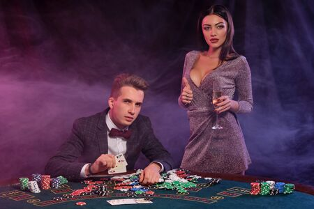 Man playing poker at casino sitting at table with stacks of chips, money, champagne, cards. Celebrating win with woman. Black background. Close-up. Stok Fotoğraf