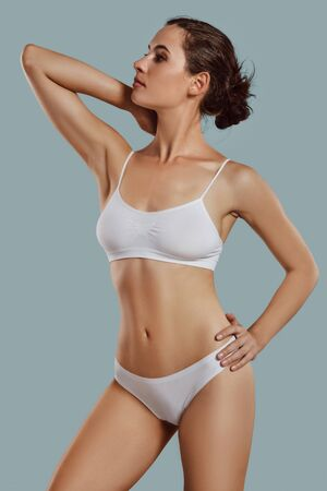 Young woman in white underwear, with bundled hair, posing in studio against gray background. Plastic surgery, aesthetic cosmetology. Close-up.