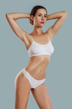 Young woman in white underwear, with bundled hair, put hands on head, posing on gray background. Plastic surgery, aesthetic cosmetology. Close-up.