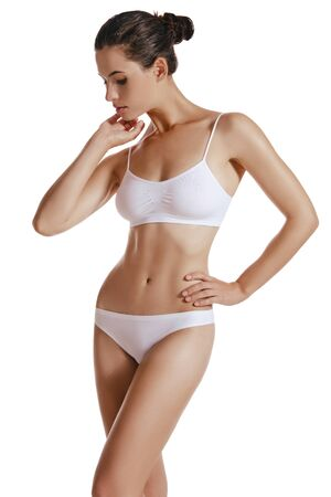 Young woman in white underwear, with bundled hair, posing in studio, isolated on white. Plastic surgery, aesthetic cosmetology. Close-up.