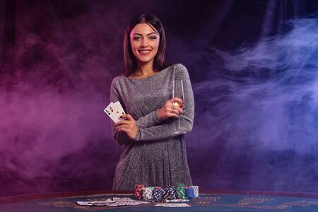 Girl playing poker at casino, holding champagne, two aces. Posing at table with chips, money, cards on it. Black, smoke background. Close-up.