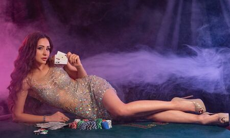 Girl in golden dress playing poker at casino, holding cards, laying on table with chips, money on it. Black, smoke background. Gambling. Close-up.